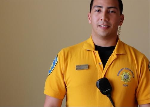 CSO in yellow shirt with emblem and badge imprint, with police radio