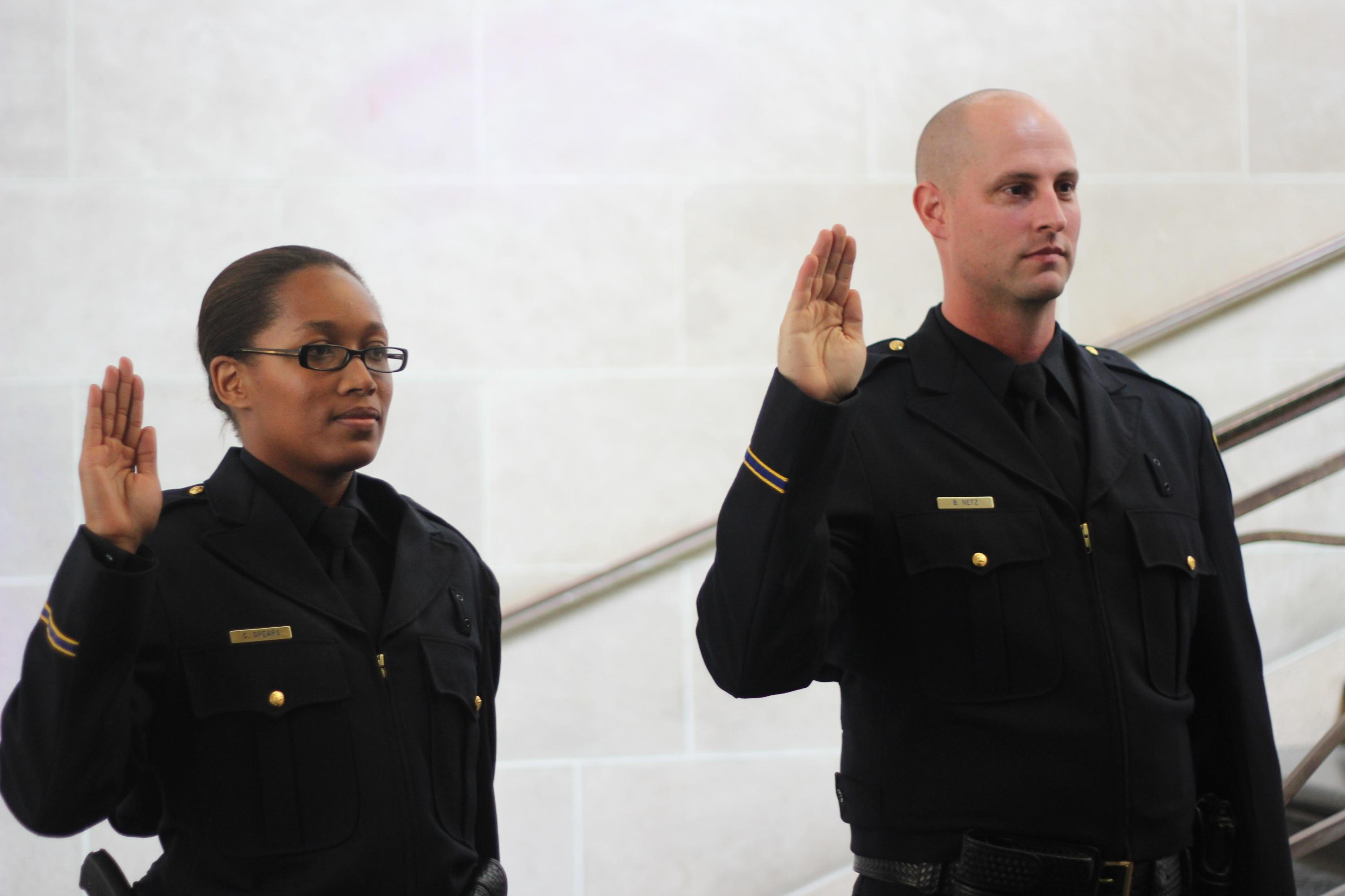 two new UCPD officers with hands up for swearing in